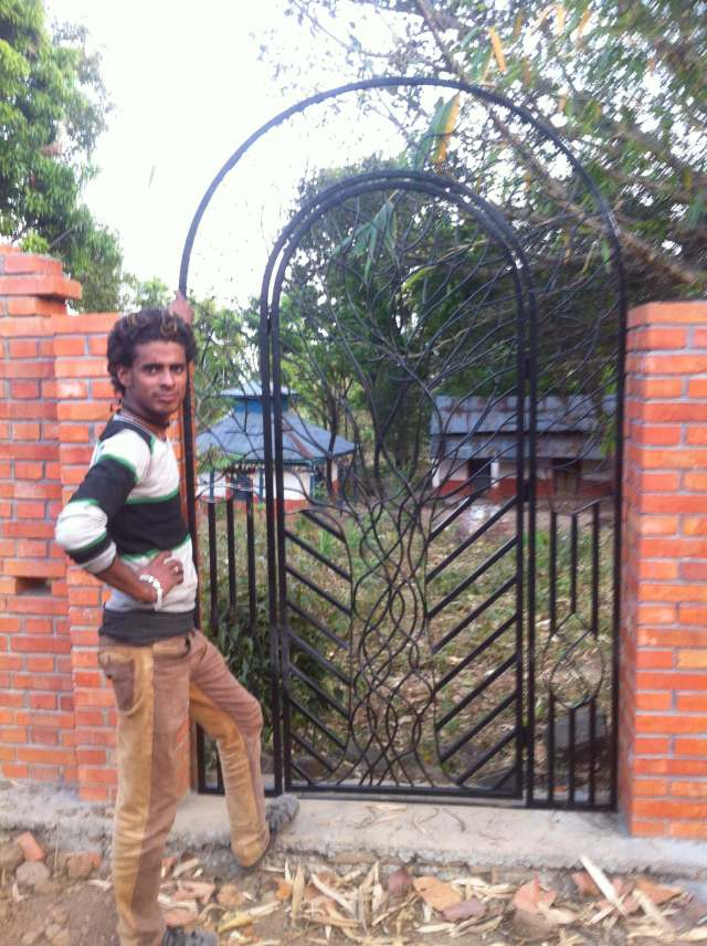 Our welder, Shalman, standing next to the gate at the land. The temple is behind.